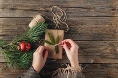 Menina que envolve o presente do Natal Mãos do ` s da mulher que guardam o soldado decorado Fotografia de Stock