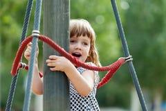Menina que escala em cordas no campo de jogos Foto de Stock Royalty Free