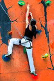 Menina que escala em uma parede de escalada Imagens de Stock