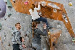 Menina que escalam uma parede com apertos e sua mamã que apoia a de fotografia de stock royalty free