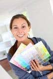 Menina que escolhe a cor da pintura Fotografia de Stock Royalty Free