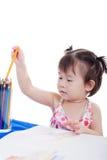 Menina que escolhe o lápis da cor para a imagem da tração Imagens de Stock