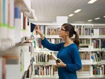 Menina que escolhe o livro na biblioteca Foto de Stock