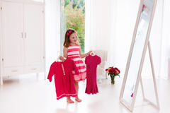 Menina que escolhe vestidos no quarto branco Fotografia de Stock Royalty Free