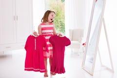 Menina que escolhe vestidos no quarto branco Fotos de Stock