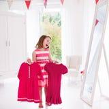 Menina que escolhe vestidos no quarto branco Imagem de Stock