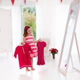 Menina que escolhe vestidos no quarto branco Fotos de Stock Royalty Free