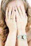 Menina que esconde atrás de suas mãos Fotos de Stock
