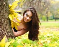 Menina que esconde atrás de uma árvore Fotografia de Stock