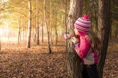 Menina que esconde atrás de uma árvore imagem de stock