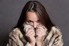 Menina que esconde no casaco de pele Fotos de Stock