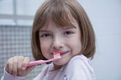 Menina que escova seus dentes no banheiro fotografia de stock