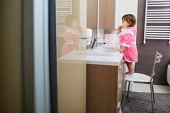 Menina que escova seus dentes no banheiro imagem de stock royalty free