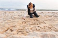 Menina que escreve o ano novo na areia Fotos de Stock