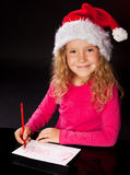 Menina que escreve uma letra a Papai Noel Fotografia de Stock Royalty Free