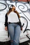 Menina que escuta a música ao inclinar-se em uma parede Imagem de Stock Royalty Free