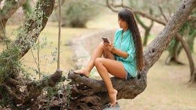 A menina que escuta a música e canta emocional e a movimentação no smartpho vídeos de arquivo