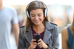Menina que escuta a música e que anda na rua foto de stock