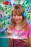 Menina que escuta a música na tabuleta Imagens de Stock