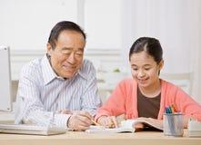 A menina que escuta o avô explica trabalhos de casa Fotografia de Stock
