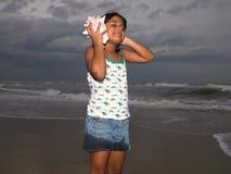 Menina que escuta o conch Fotografia de Stock Royalty Free
