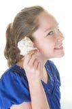 Menina que escuta o seashell fotografia de stock royalty free