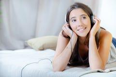 Menina que escuta os fones de ouvido colocados na cama imagem de stock royalty free