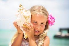 Menina que escuta um seashell Fotografia de Stock