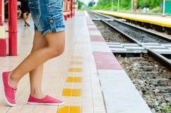 Menina que espera o trem atrás da linha amarela Fotografia de Stock Royalty Free