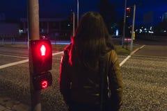 A menina que espera para cruzar uma rua na luz vermelha da noite está brilhando imagens de stock