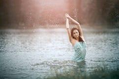 Menina que espirra a água no lago por suas mãos movimento foto de stock