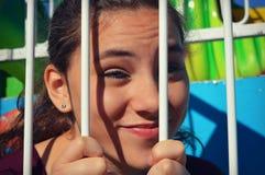Menina que espreita através das barras fotos de stock royalty free