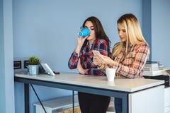 Menina que espreita no telefone celular dos colegas ao beber o café imagem de stock