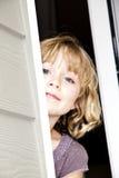 Menina que espreita para fora a porta fotos de stock
