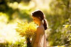 Menina que está com um ramalhete dos wildflowers fotografia de stock royalty free