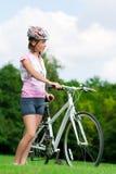 Menina que está com uma bicicleta Foto de Stock Royalty Free