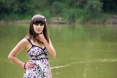 Menina que está e que levanta perto do rio Foto de Stock Royalty Free