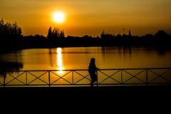 Menina que está em público o parque durante o por do sol bonito Foto de Stock