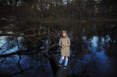 Menina que está em uma árvore caída perto da lagoa na mola adiantada Imagens de Stock Royalty Free