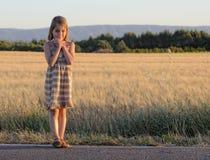 Menina que está na borda da estrada Imagem de Stock