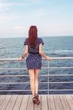Menina que está na doca que olha o oceano do mar Foto de Stock