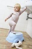 Menina que está na etapa no banheiro para alcançar o dissipador fotos de stock
