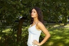 Menina que está na frente de uma árvore magnífica Foto de Stock Royalty Free