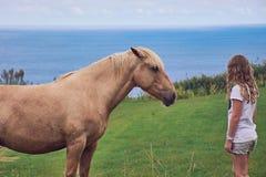 Menina que está na frente de uma luz - cavalo marrom fotografia de stock