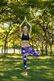 Menina que está na pose da ioga do vrikshasana Foto de Stock