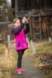 Menina que está na rua que toma um selfie em um smartphone Imagem de Stock