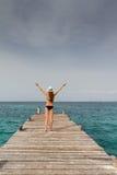 Menina que está no cais que aumenta seus braços para o céu Fotos de Stock Royalty Free