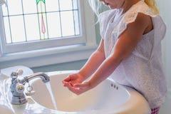 Menina que está no tamborete da etapa que lava suas mãos no banho fotografia de stock royalty free