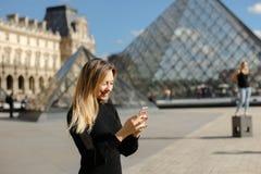 Menina que está o Louvre próximo e o pyramind de vidro no vestido preto em Paris, texting pelo smartphone fotos de stock