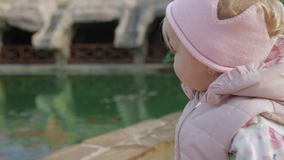 Menina que está perto da lagoa com os peixes vídeos de arquivo